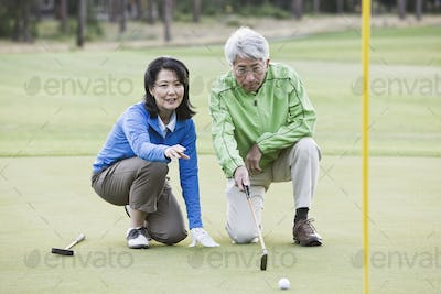 Asian senior couple taking a look at the direction of the next putt on the green.