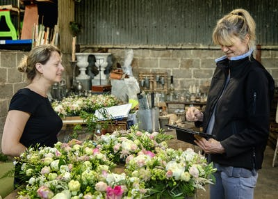 Two women, one using a digital tablet. Florists at a workbench covered in table decorations, pink