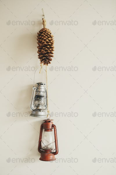 Two hurricane lamps and a pine cone hanging on a wall.