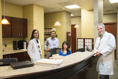 Caucasian male and east Indian woman ophthalmologists in their office with their staff employees.