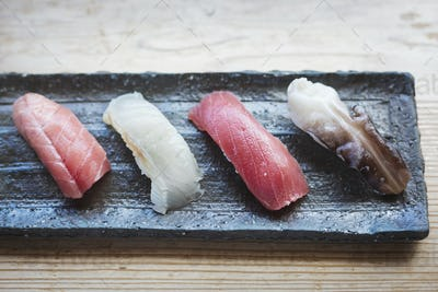 High angle close up of four pieces of sushi served on a rectangular dish.