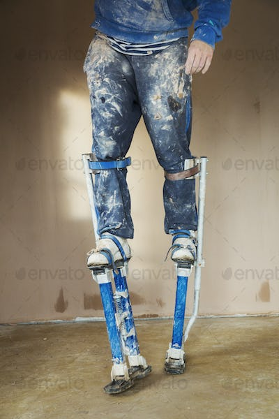 A plasterer wearing stilts working on the walls of a house under construction.