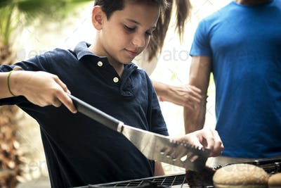 A boy holding tongs and turning food on a barbecue.