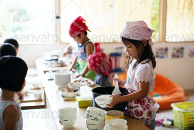 A girl and a boy wearing headscarves standing at a table in a Japanese preschool, serving lunch.