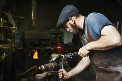 A blacksmith in a leather apron bends a cone of red hot metal in a vice using a wrench and a pair of
