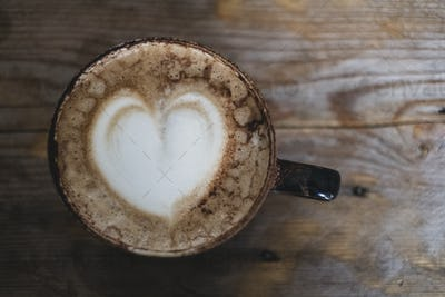 High angle close up of cappuccino topped with foam heart.
