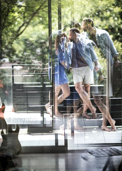 A couple standing on a balcony kissing, seen through a glass door.
