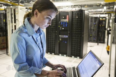 Caucasian woman technician running diagnostics on computer servers in a server farm.