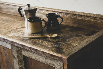 High angle close up of Espresso maker, earthenware mug and jug and wooden spoon on vintage wooden