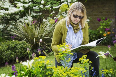 Woman wearing sunglasses standing in a garden by a flowerbed, drawing in a sketchbook.