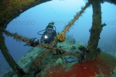 Scuba diver investigates the wreckage of an airplane dating from World War Two on the seabed in