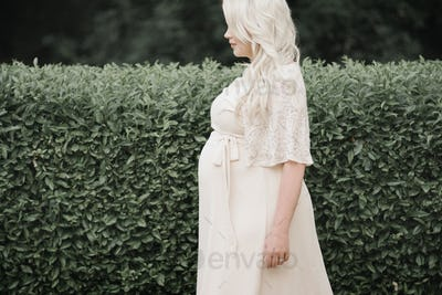 Portrait of a pregnant woman with long blond hair in a garden.