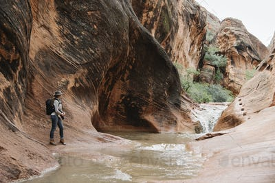 Woman standing by river in a canyon.