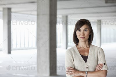 Caucasian businesswoman in a large empty raw office space.