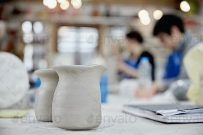 Two clay jugs in the foreground. A ceramics class taking place, people seated at a workbench in a