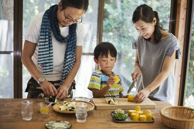Man, woman and boy standing at a table, preparing corn on the cob, smiling.
