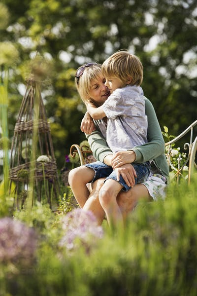 Woman sitting in a garden with a boy on her lap, hugging.
