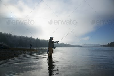Silhouette of fisherman fly fishing for salmon and sea run cutthroat trout in Puget Sound near