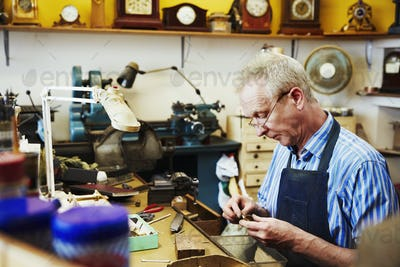 A clock maker working repairing the small parts of a clock.