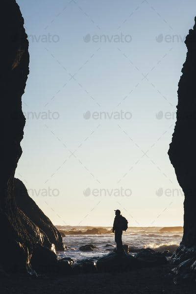 Silhouette of man standing between tall cliffs at dusk, the Pacific Ocean in the distance, Olympic
