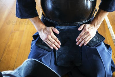 Close up of Kendo fighter kneeling on floor, hands on lap.