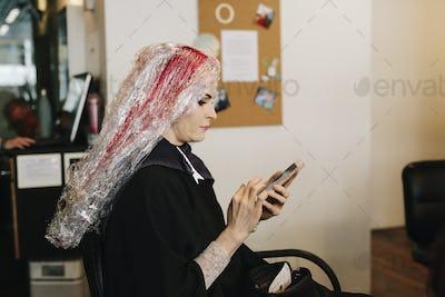 A woman in a hair salon having a hair colour treatment, using a smart phone.