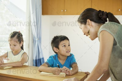 A teacher talking to two children sitting at a desk.