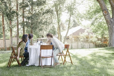 Group of women sitting round a table in a garden.
