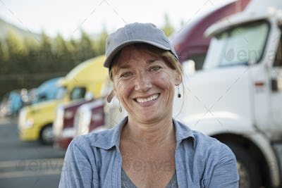A caucasian woman truck driver near her truck parked in a parking lot of a truck stop.