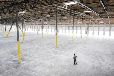 Owner checking out the new interior of a large empty warehouse space.