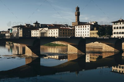 The Ponte alle Grazie, historic bridge over the flat calm water of the River Arno, in the middle of