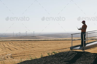 A wind farm technician standing and using a laptop at the base of a turbine on a wind farm in open