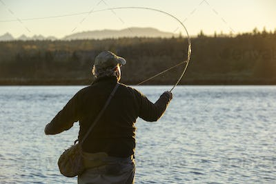 A view from berhind of a fly fisherman casting for salmon and searun coastal cutthroat trout from a