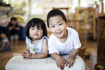 Smiling boy and girl in a Japanese preschool, looking at camera.