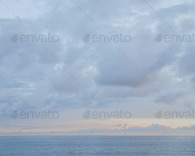 View to the horizon, clouds in the sky and gathering dusk. Sunset light on the horizon.