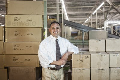 Portrait of a male Hispanic American executive in a shirt and tie surrounded by products stored in