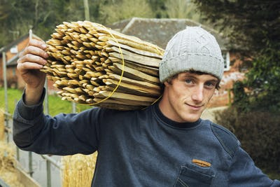 Thatcher carrying a bundle of wooden pegs used for thatching a roof.