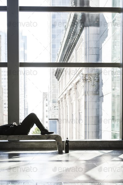 Business man taking a break laying on a bench in a large open lobby area.