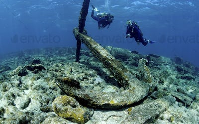 Two scuba divers swimming over a large anchor on the wreck of a ship on the seabed.