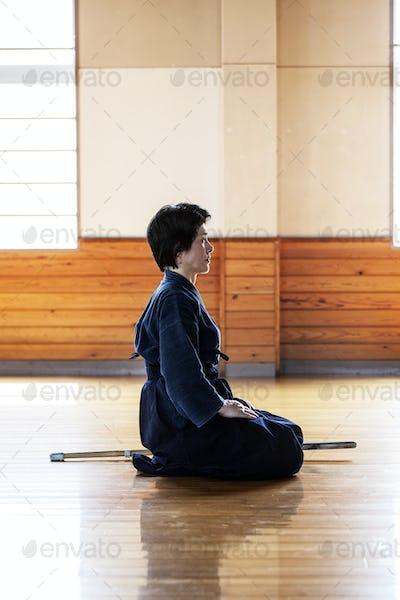 Side view of female Japanese Kendo fighter kneeling on wooden floor.