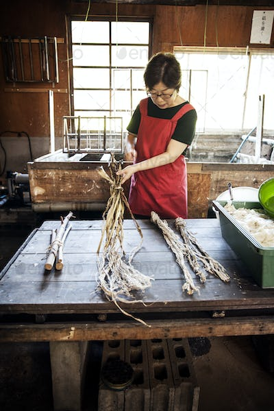 Woman standing at a table in a traditional Washi workshop, stripping bark and fibre off twigs and