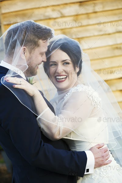 A bride and groom, a young woman laughing and draping her veil over her husband's head.