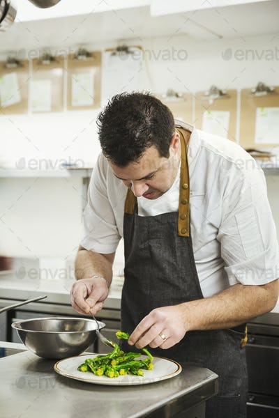 Chef standing in the kitchen in a small hotel, plating up a dish of vegetables.