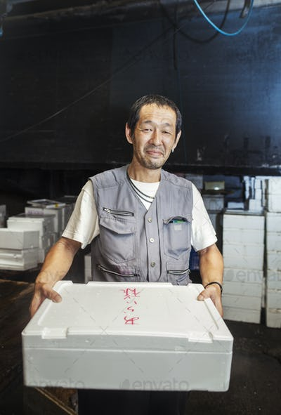 A traditional fresh fish market in Tokyo. A man holding a box of fresh fish on ice.