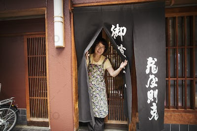 A small artisan producer of specialist treats, sweets called wagashi. A woman at the doorway of the