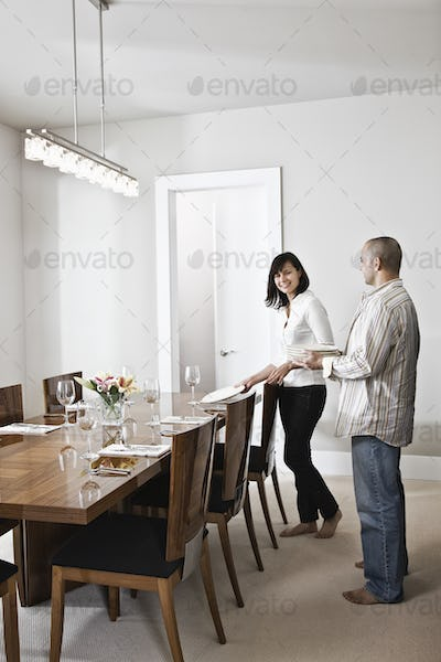 Hispanic man and woman doing place settings at their dinning room table in a new home.