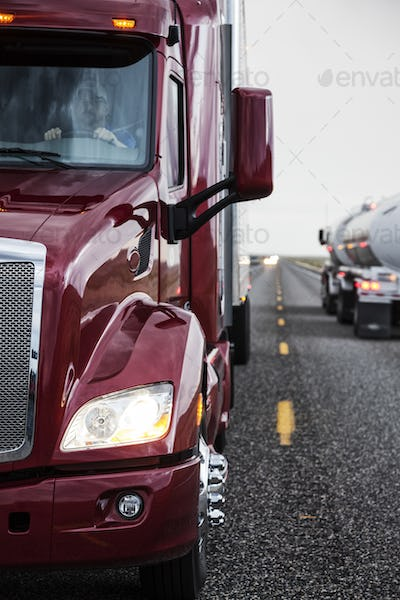 Close up view of the cab and driver of a  commercial truck on the highway.