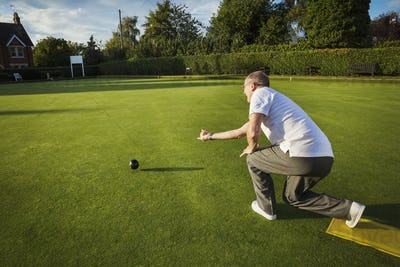 A lawn bowls player standing on a small yellow mat preparing to deliver a bowl down the green, the