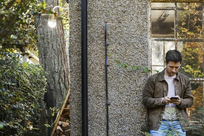 A young man using a smart phone standing in a courtyard.