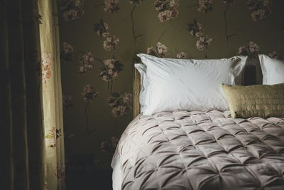 Interior view of bedroom with curtains and wallpaper with floral pattern, pale pink quilt and white